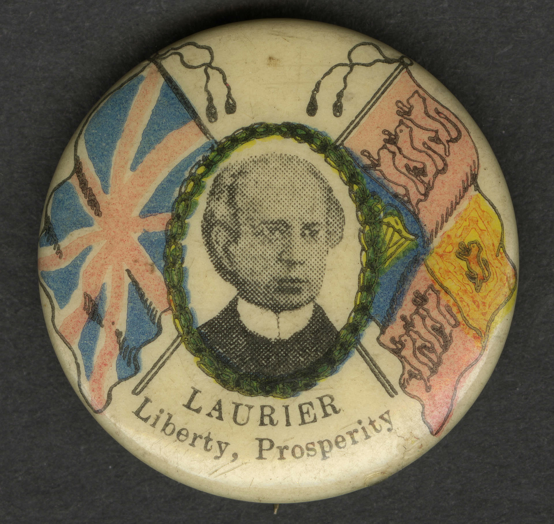 """photo of a button showing a man's face, with the words """"Laurier: Liberty, Prosperity"""""""