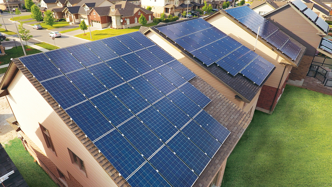 a series of four homes with solar panel roofs