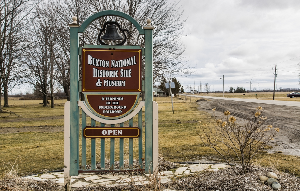 A green and brown wooden sign indicating the entrance to Buxton National Historic Site and Museum.