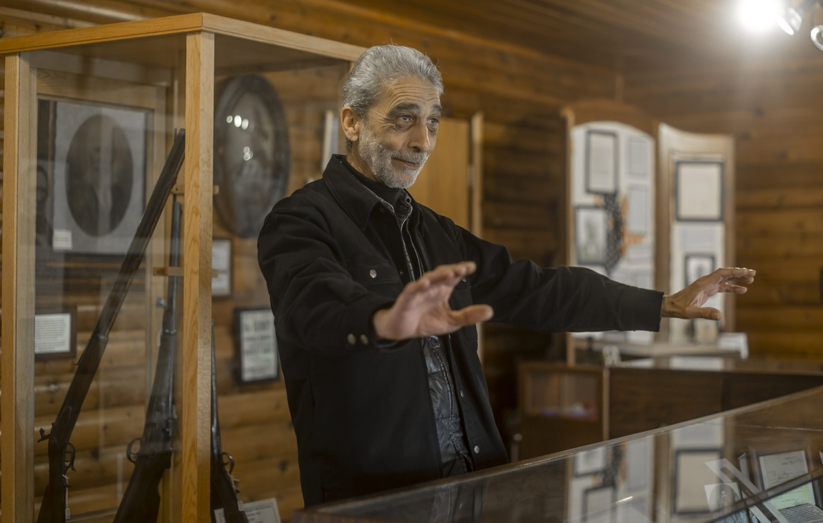 Spence Alexander stands in front of a glass case that houses artifacts from the historic settlement.