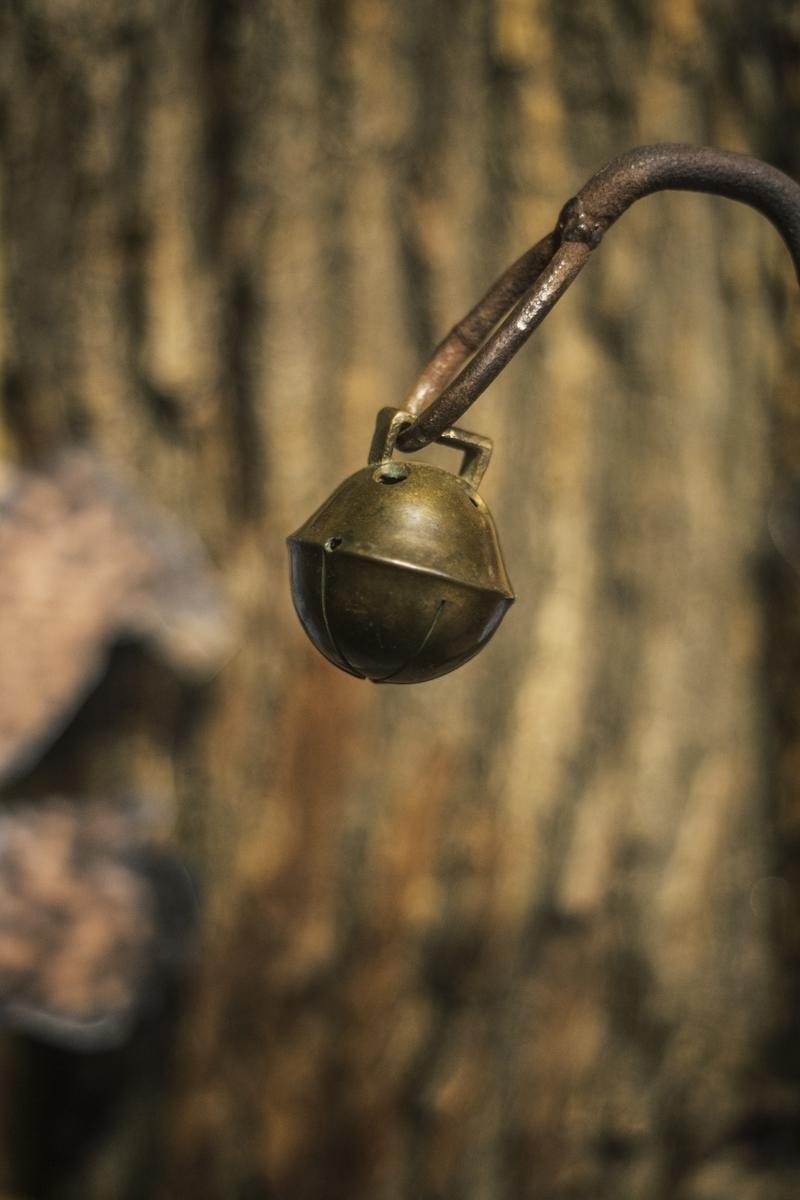 A single ball-shaped brass bell hangs from a metal hook.