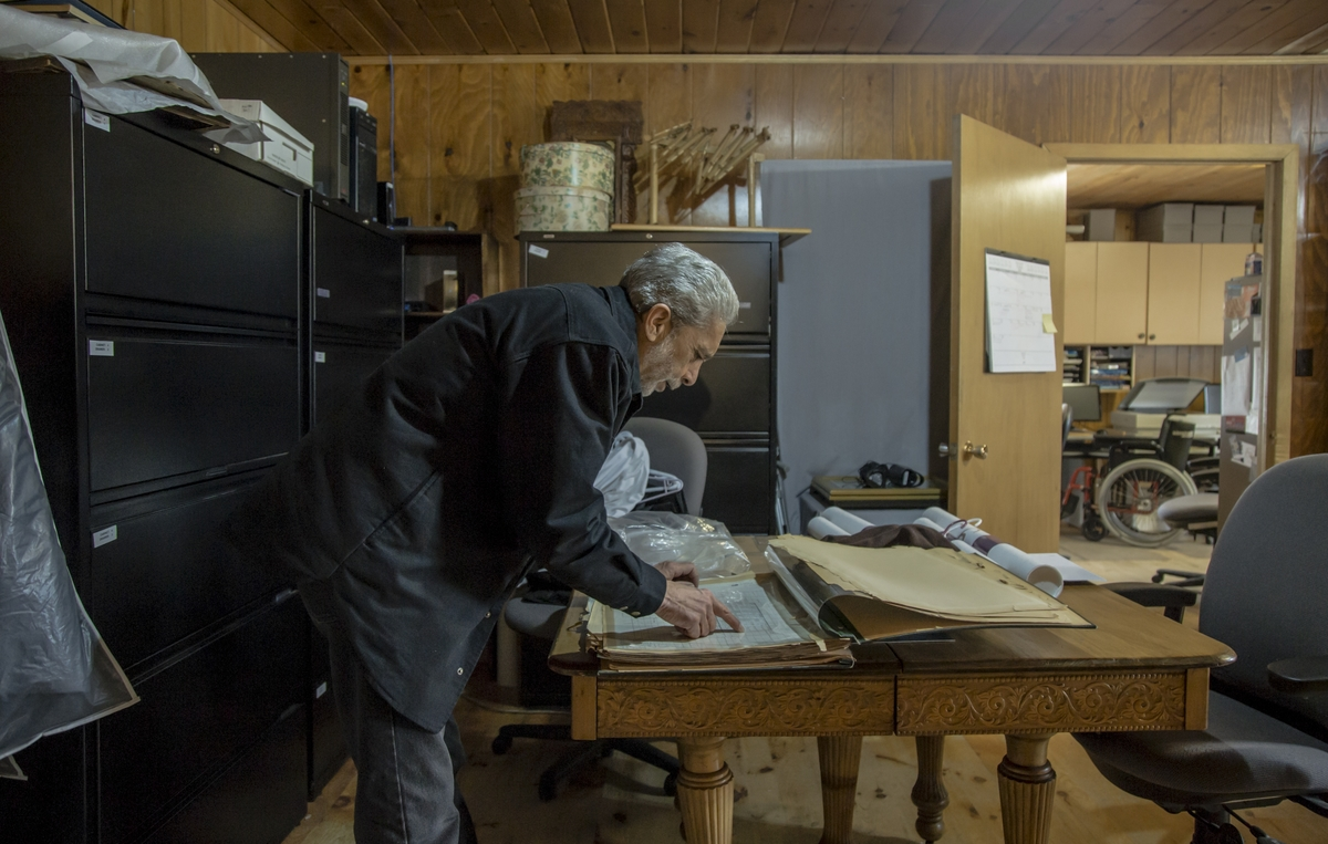 Alexander Spence looks through a large book of old maps in a room full of filing cabinets.