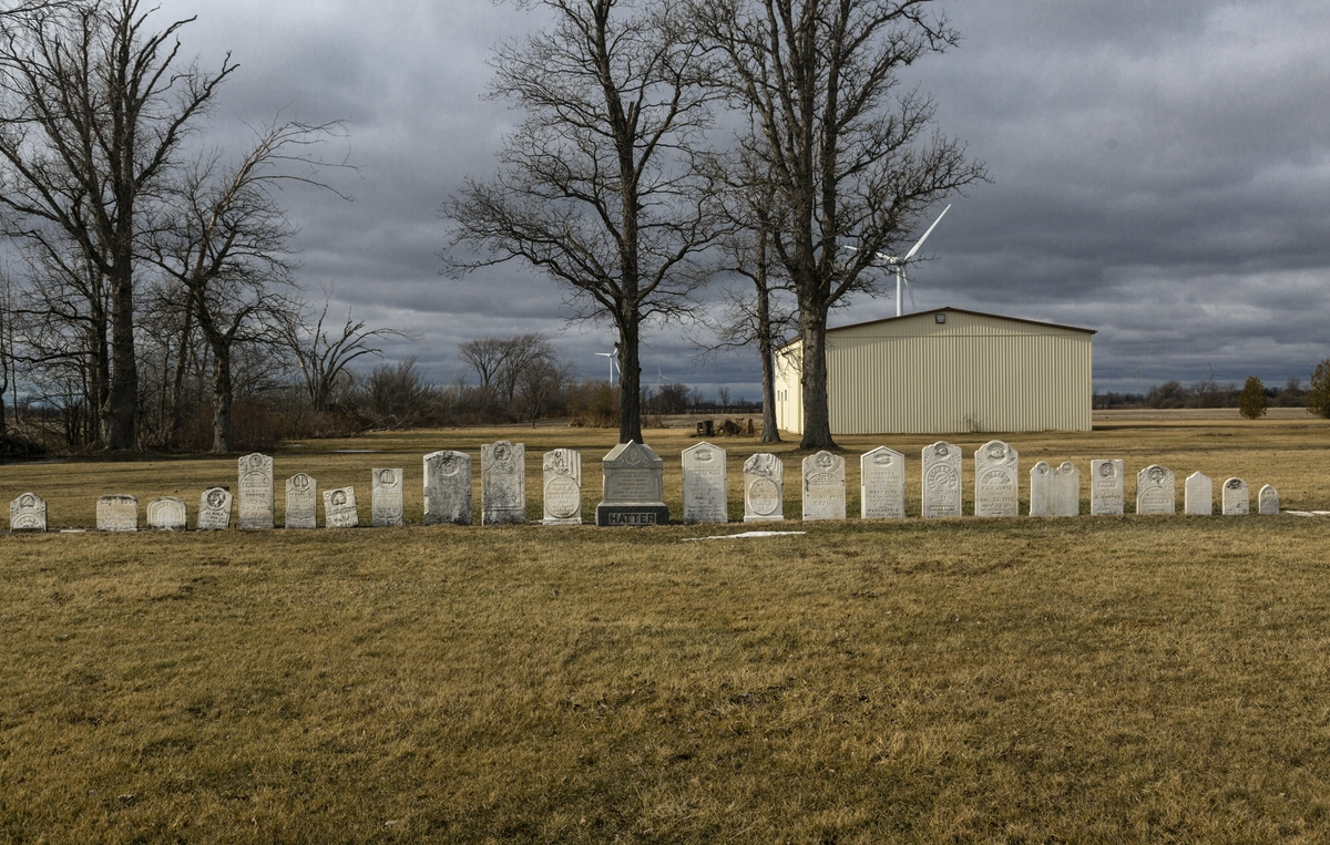 A field on an overcast/cloudy day with 15 tombstones, in varying shapes and sizes, lined up in a horizontal row.