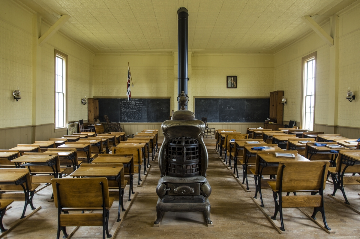 A nineteenth century classroom with wooden stove in the middle and rows of desks.