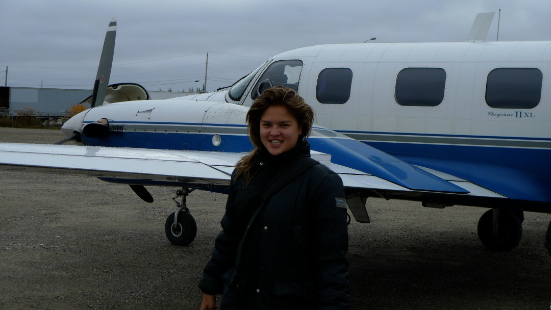 Alexandra Shimo, author and journalist, standing in front of an airplane