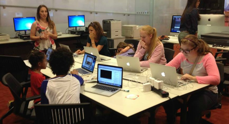 a group of young girls seated around a table learning computer technology