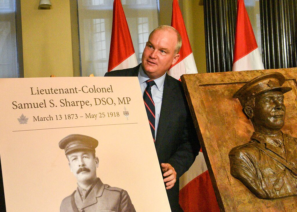 MP Erin O'Toole standing next to a plaque in honour of Samuel Sharpe.