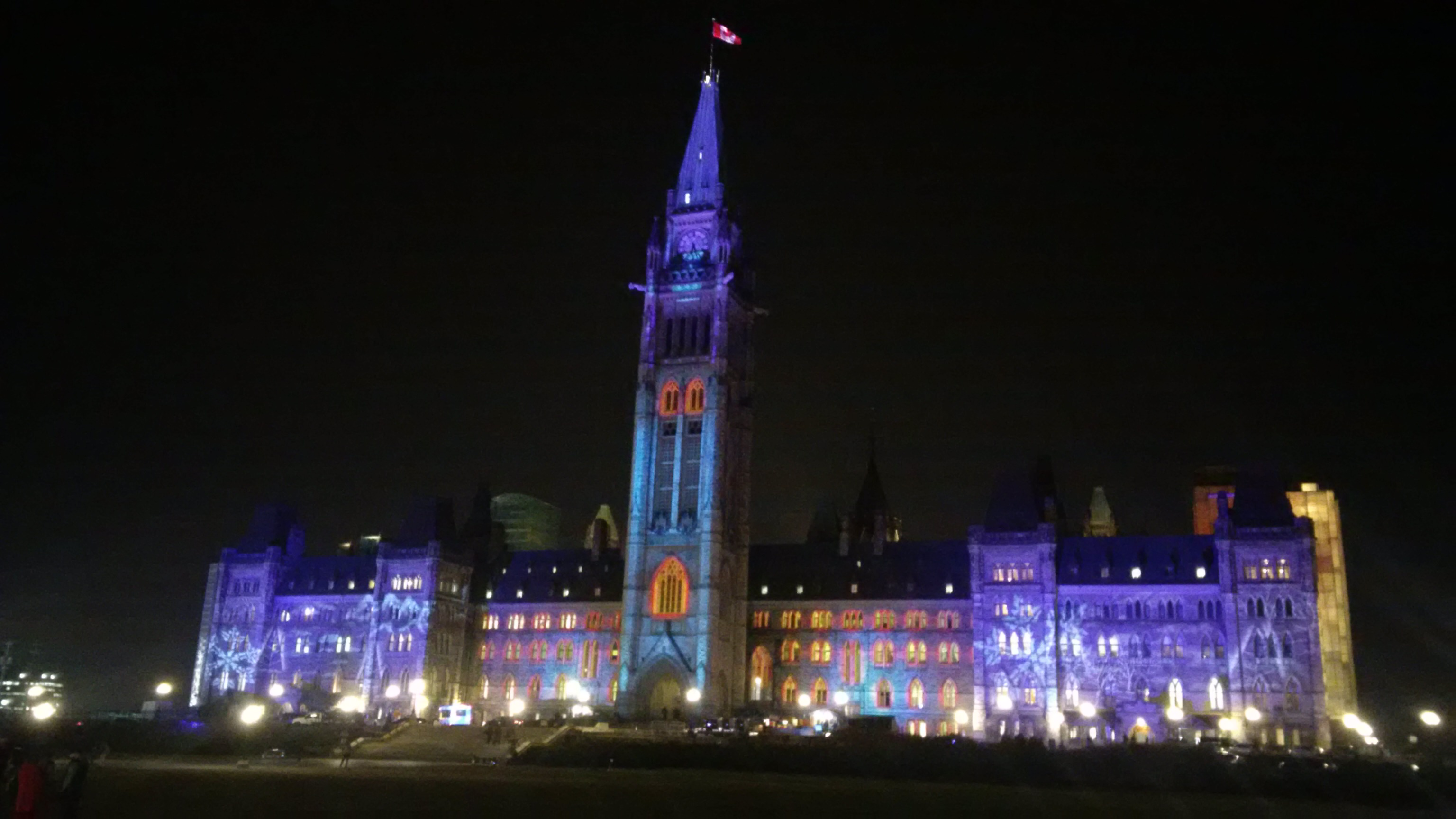 Centre Block on Parliament Hill lit up during a night-time light show.