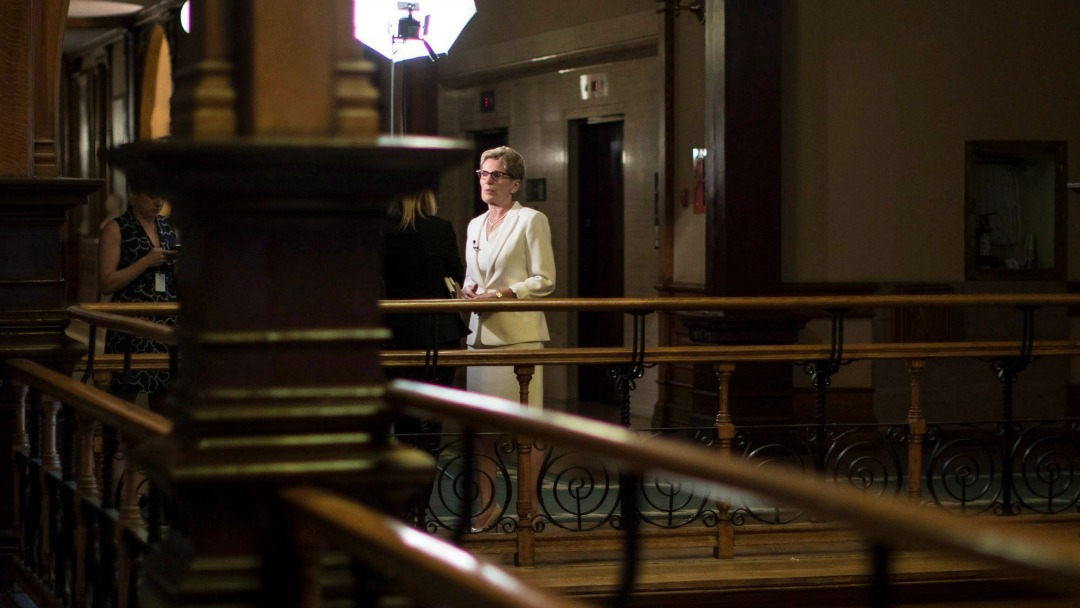 Kathleen Wynne speaks to a reporter at Queen's Park.