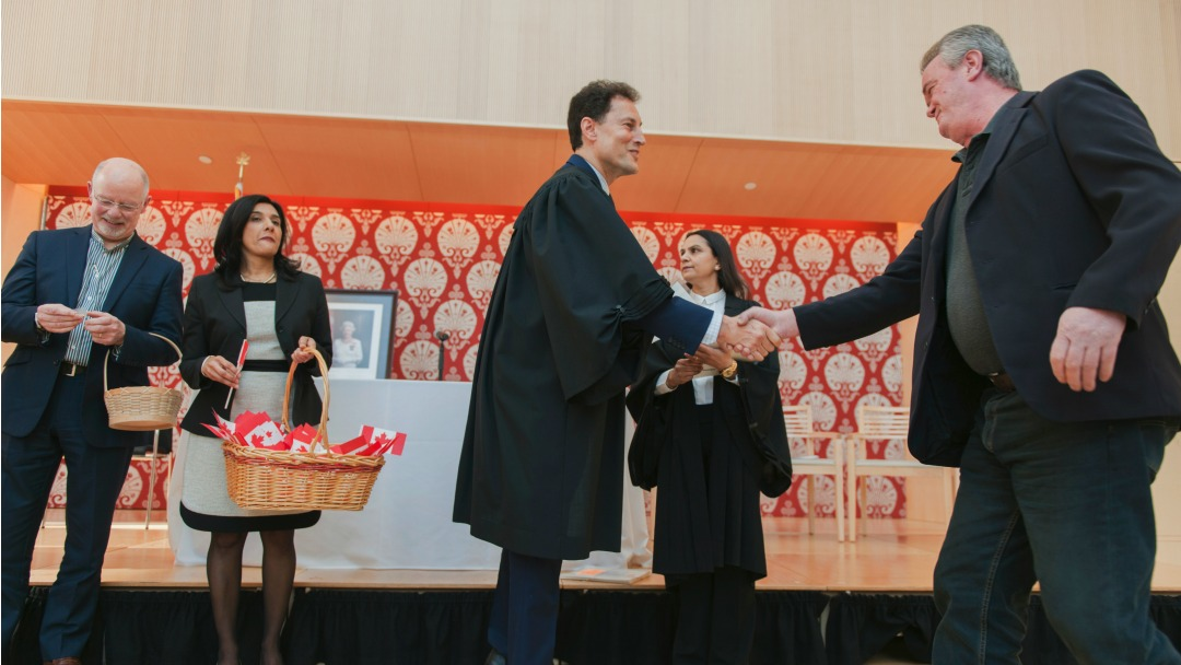 Steve Paikin shaking hands with several new Canadians after a citizenship ceremony.