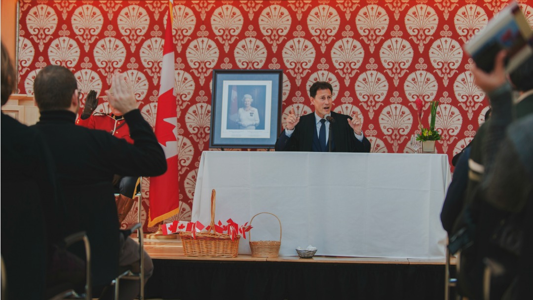 Steve Paikin at a podium in front of a group of new Canadians at a citizenship ceremony.
