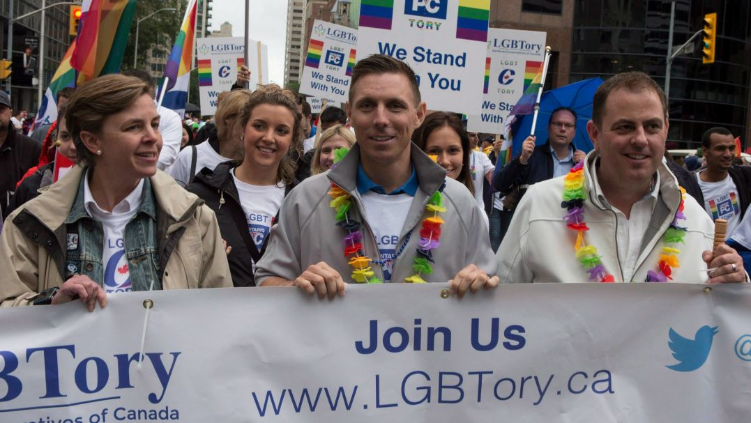 Patrick Brown holds a banner with two other people as he marches in a gay pride parade.