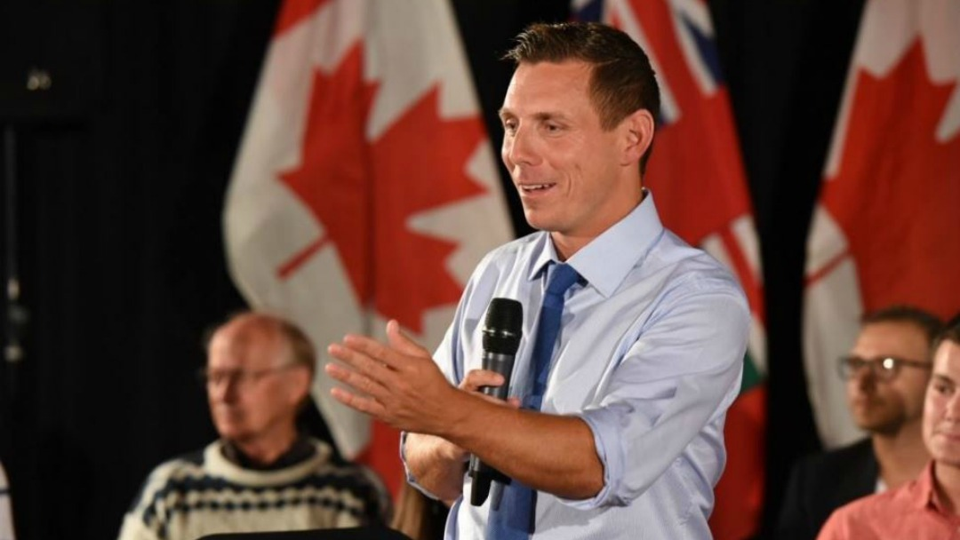 Patrick Brown holds microphone in front of Canadian flags.