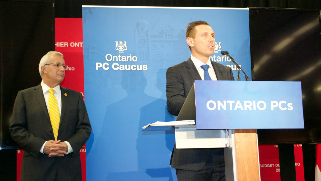 Patrick Brown speaks at podium while MPP Vic Fedeli looks on.