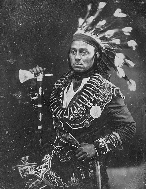 Black and white photo of man standing in traditional Indigenous clothing.