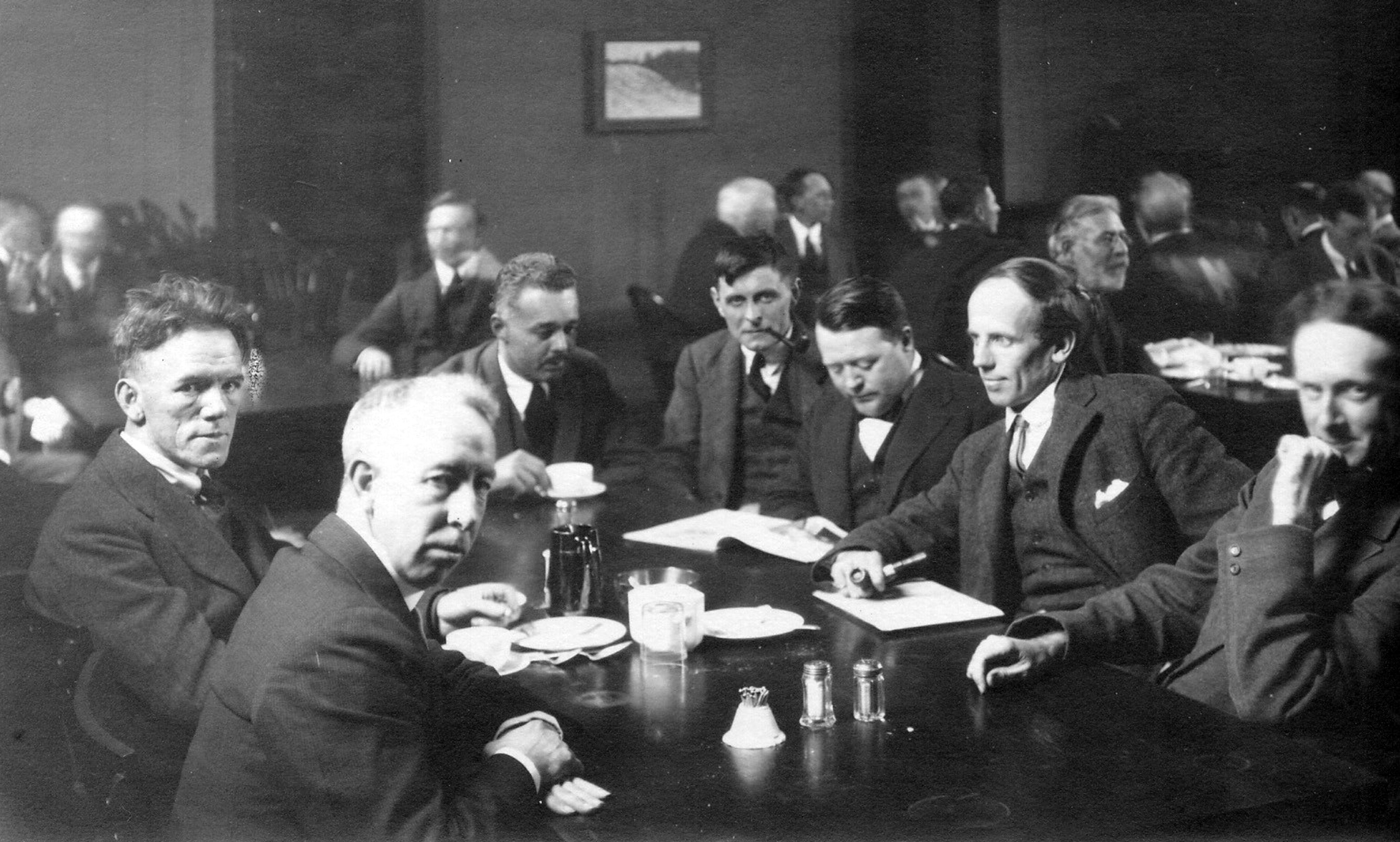 Black and white photo. Seven men seated around a table.