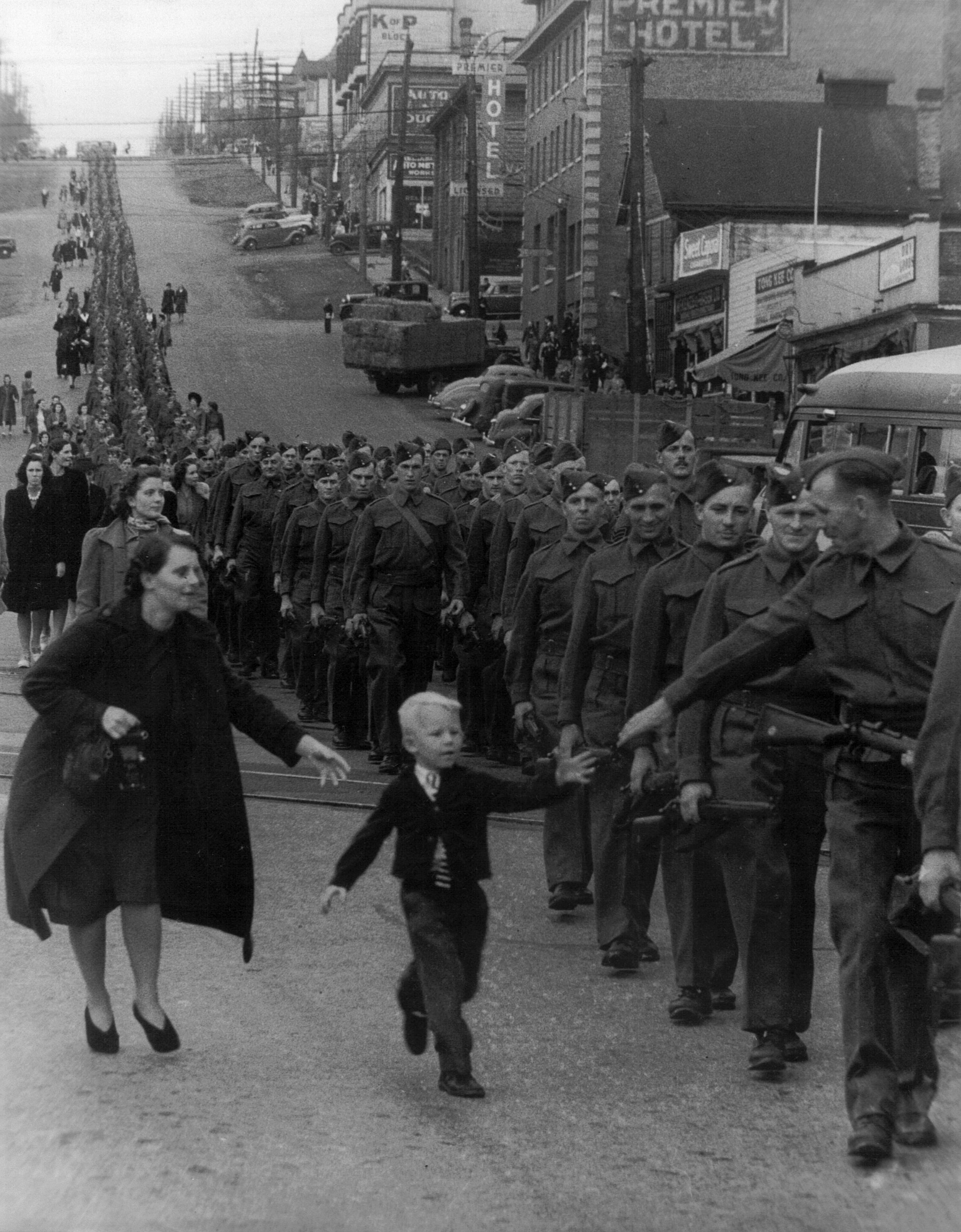 Boy reaches for father marching in a line of soldiers.