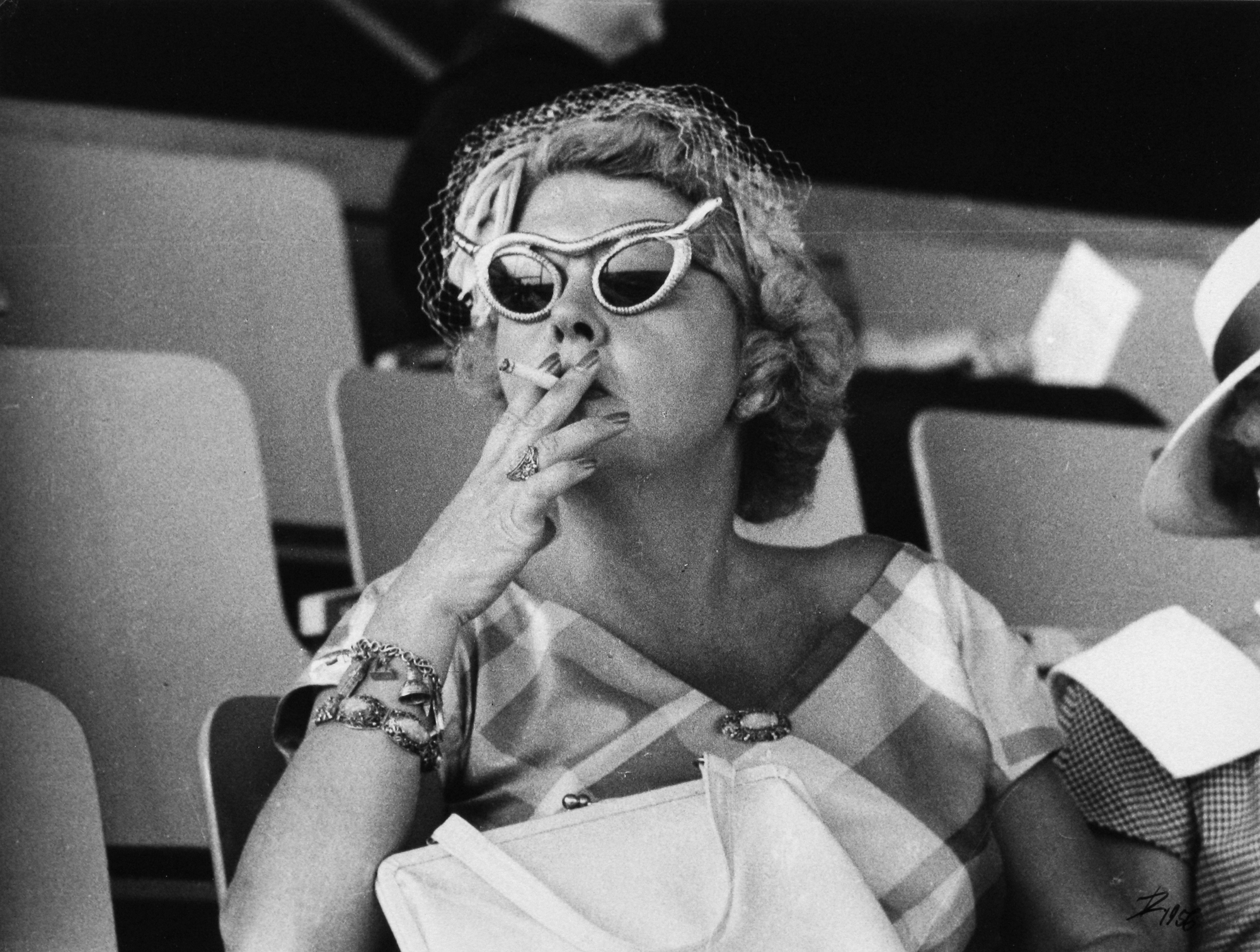 Woman sits in stands, wearing sunglasses and smoking a cigarette.