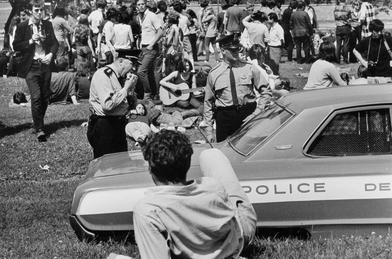 Police stand next to a patrol car as younger adults attend an event in the background.