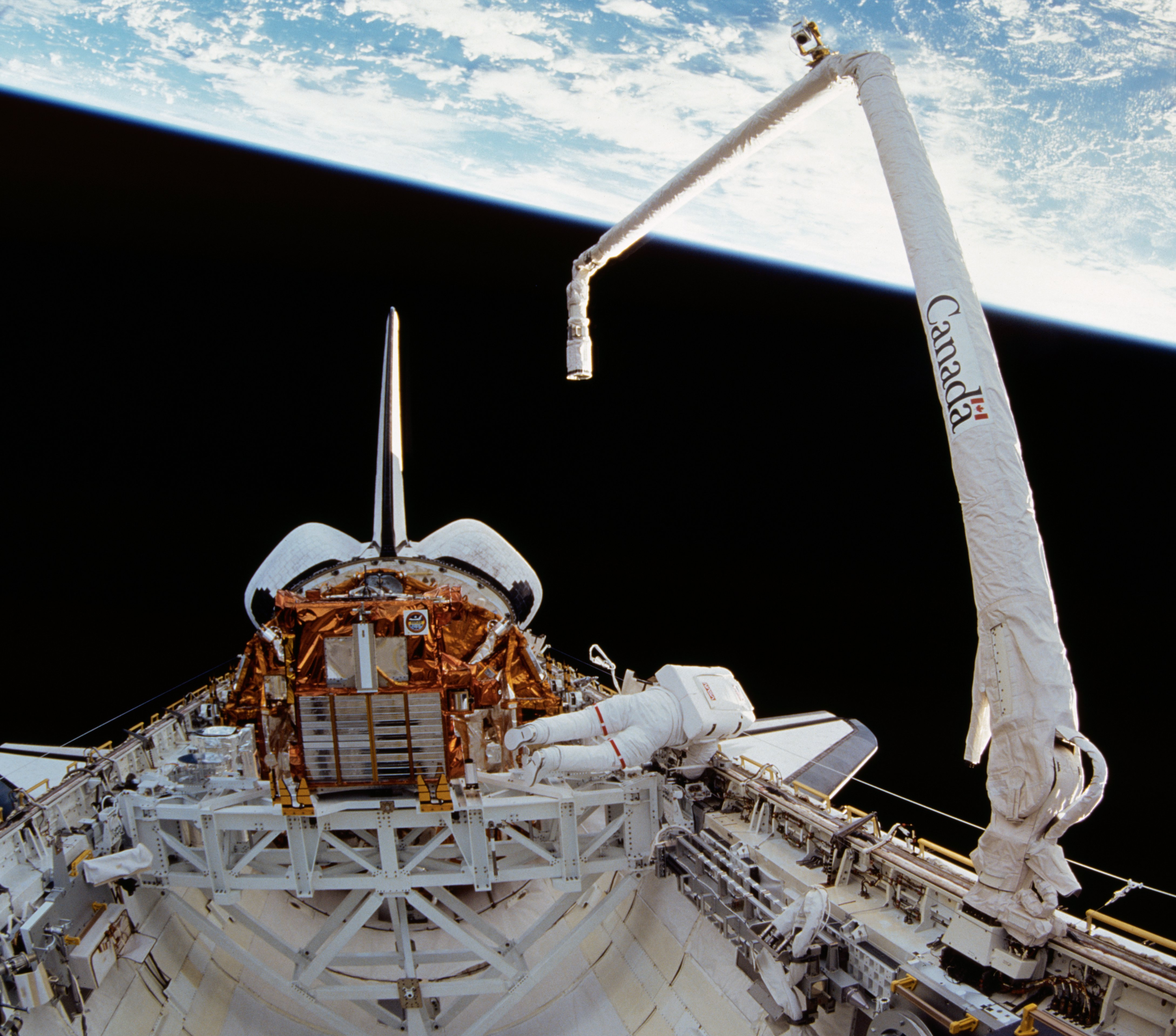 Space shuttle and Canadarm with Earth in the background.