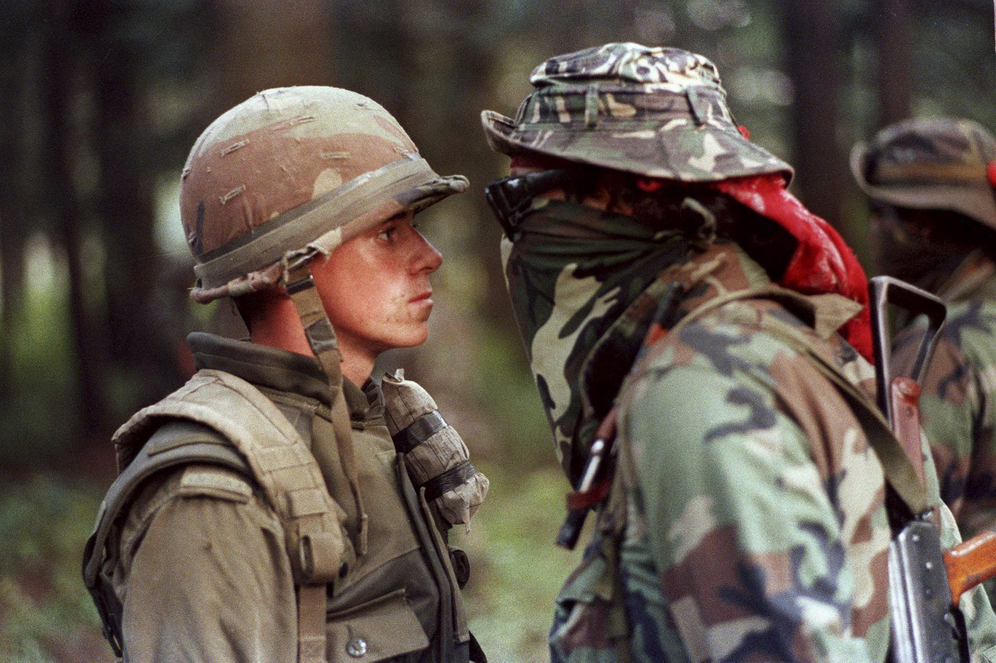 Canadian soldier stands facing indigenous protester with a bandana and sunglasses covering his face.