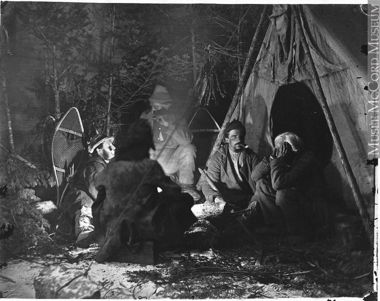 Black and white photo of four men huddled around a fire, next to a tent.