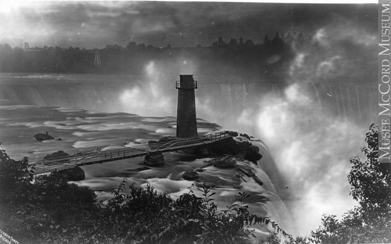 Black and white image of tower in front of large waterfall.