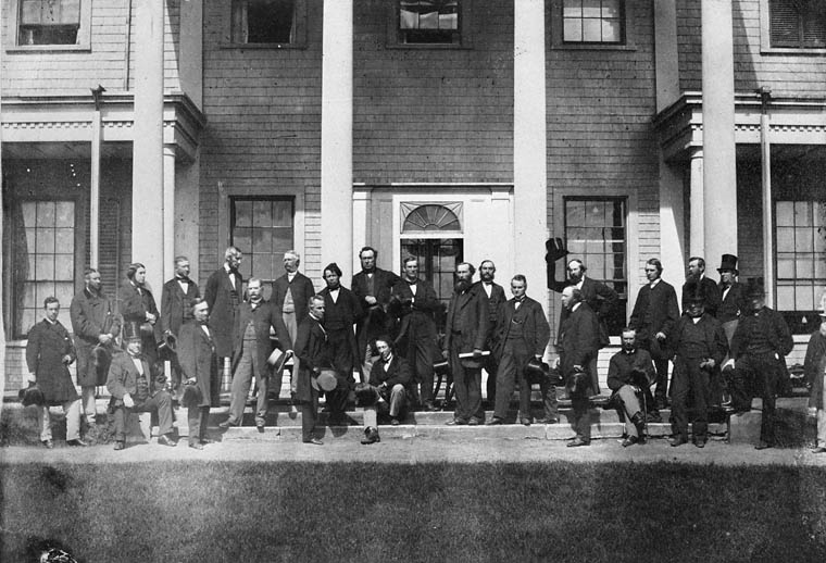 Black and white photo of about 20 men standing in front of a large building.