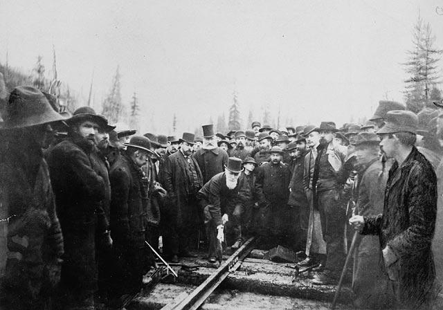 Black and white photo. Group watches man hammer a rail track.