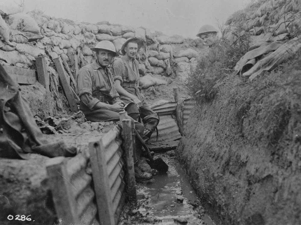 Black and white photo. Two men sit in a trench.