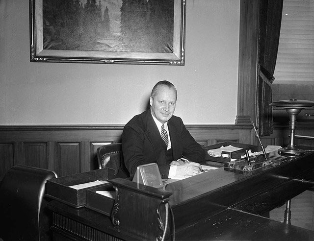 a black and white photo of a man sitting at a desk