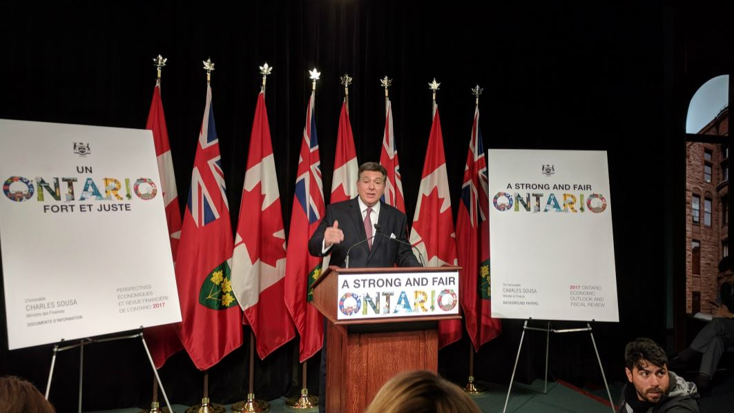 Charles Sousa stands in front of a series of Ontario and Canadian flags
