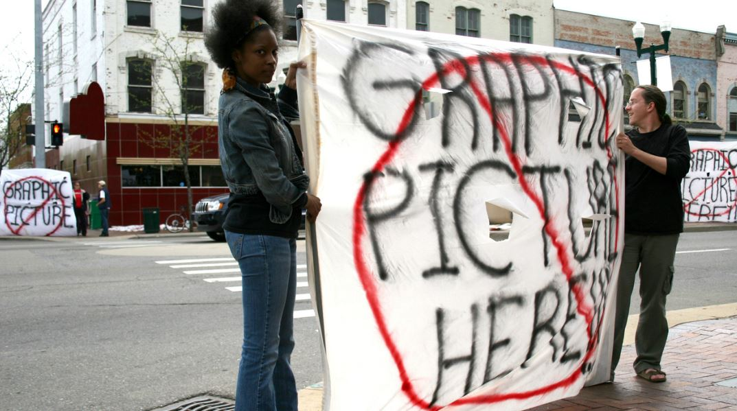 "Two people hold up sign with words ""Graphic pictures here"" barred through."