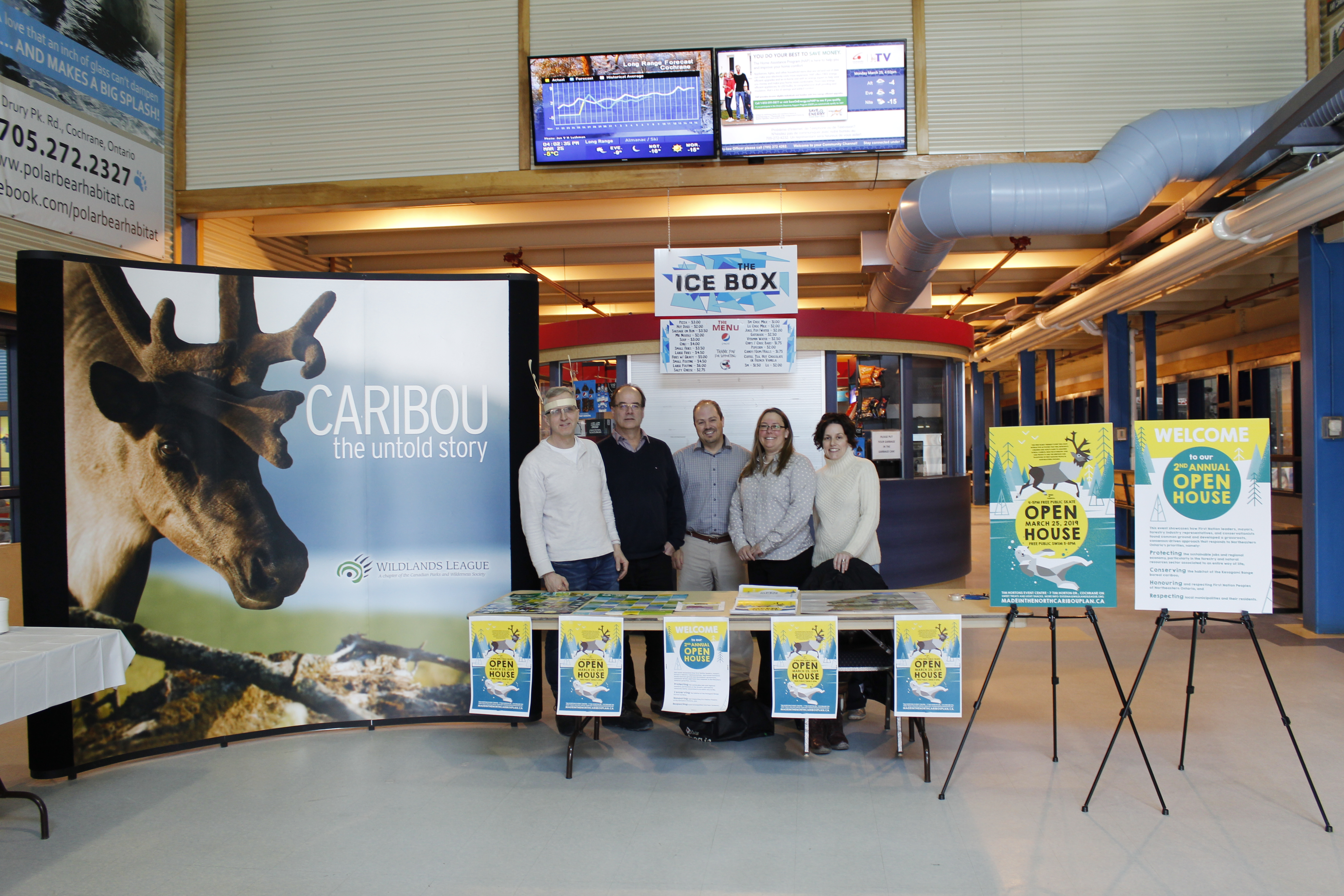 group of people standing next to a large photo of a caribou