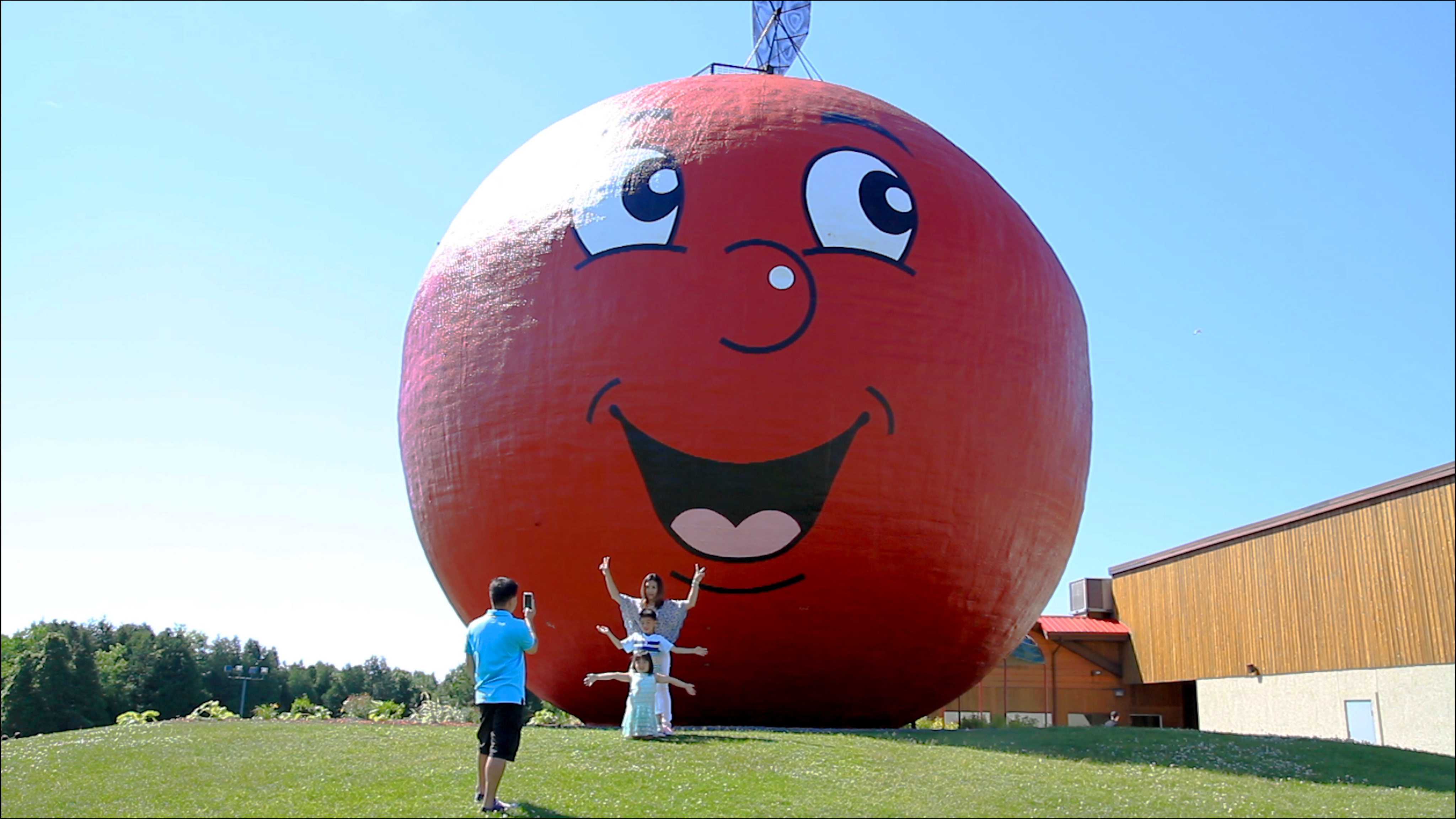 two people in front of a giant apple with a smiley face