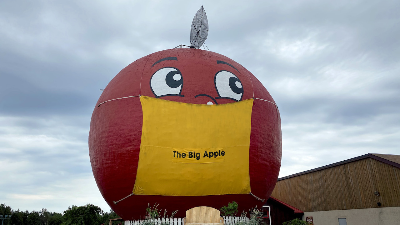 giant red apple wearing a yellow mask