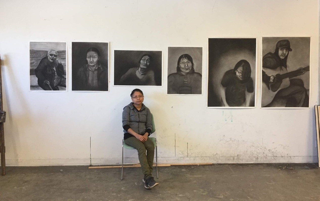 a woman sits on a chair in front of a row of paintings