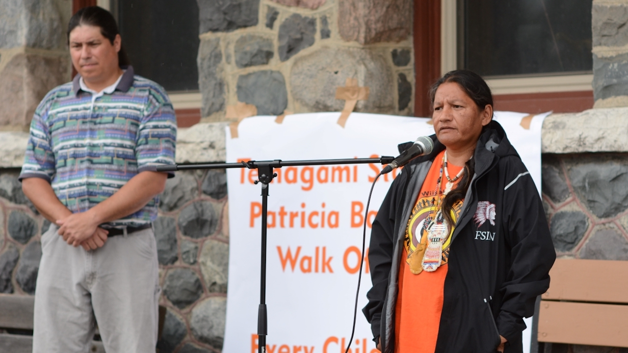 woman in orange shirt stands behind microphone while man looks on