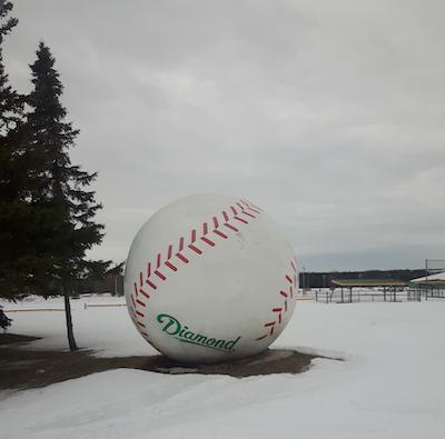 a giant baseball on snowy ground