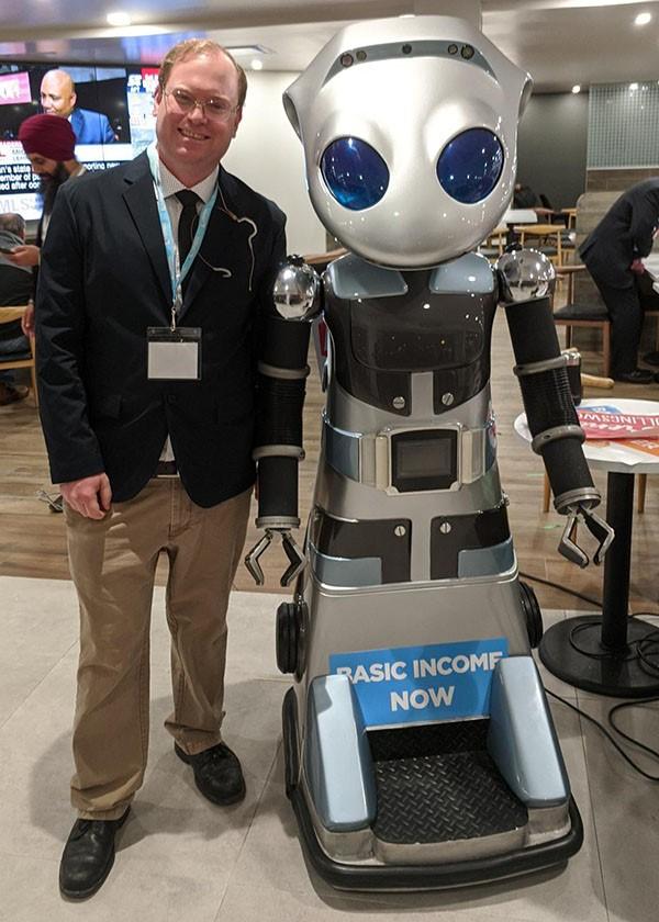 Man standing next to robot