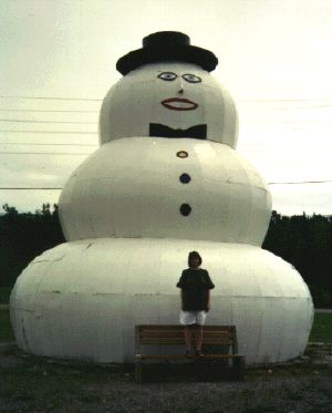 a giant snowman sculpture with a person standing in front