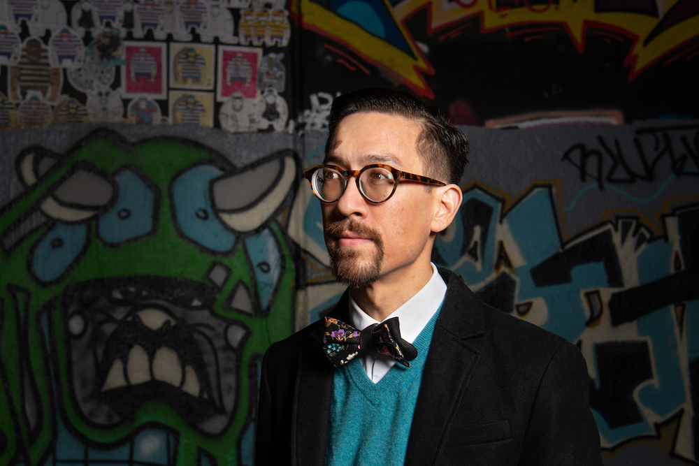 man in bowtie standing in front of graffiti