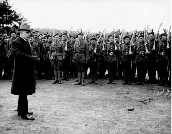 Black and white photo. Man stands in front of group of men.