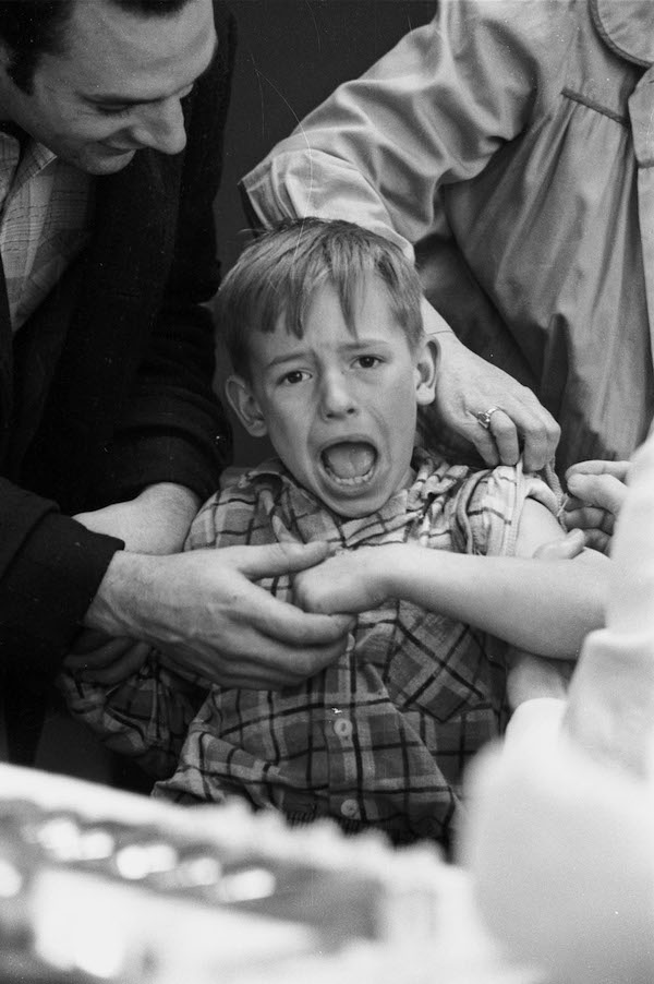 boy makes a face while getting a needle