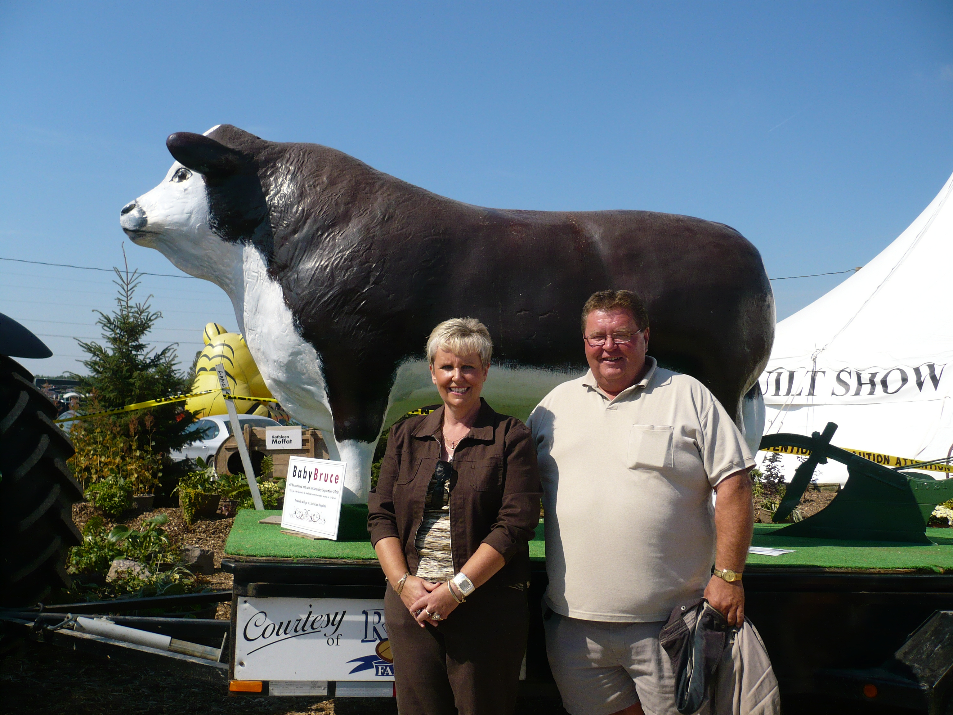 smiling man and woman in front of fibreglass bull