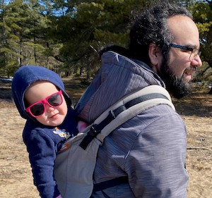 a man carrying a smiling baby on his back