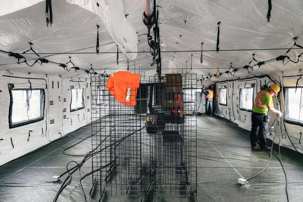 workmen in a large tent