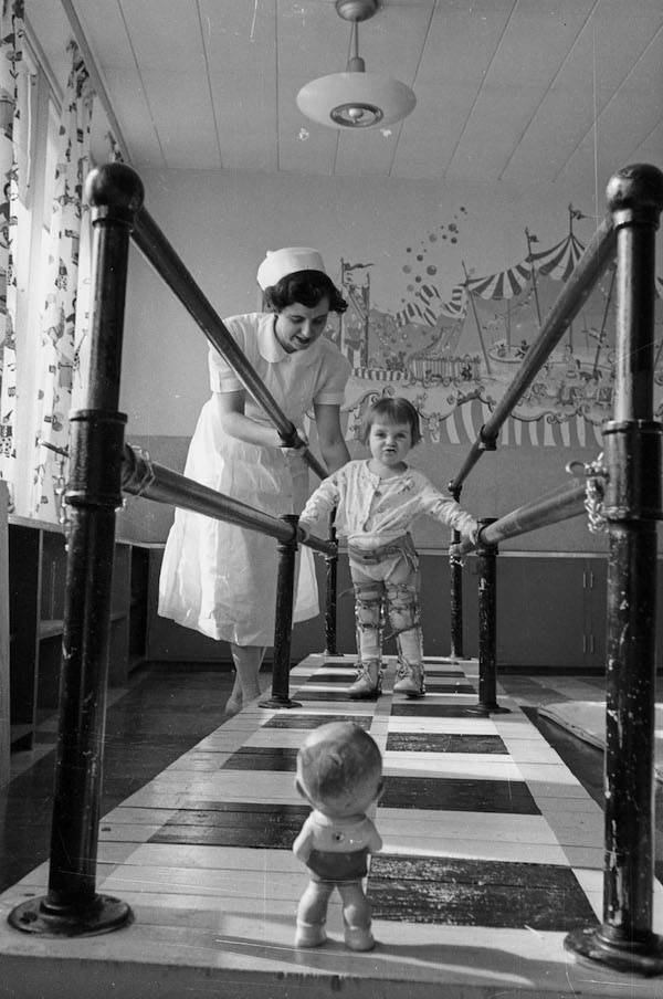 child walking while supervised by a nurse