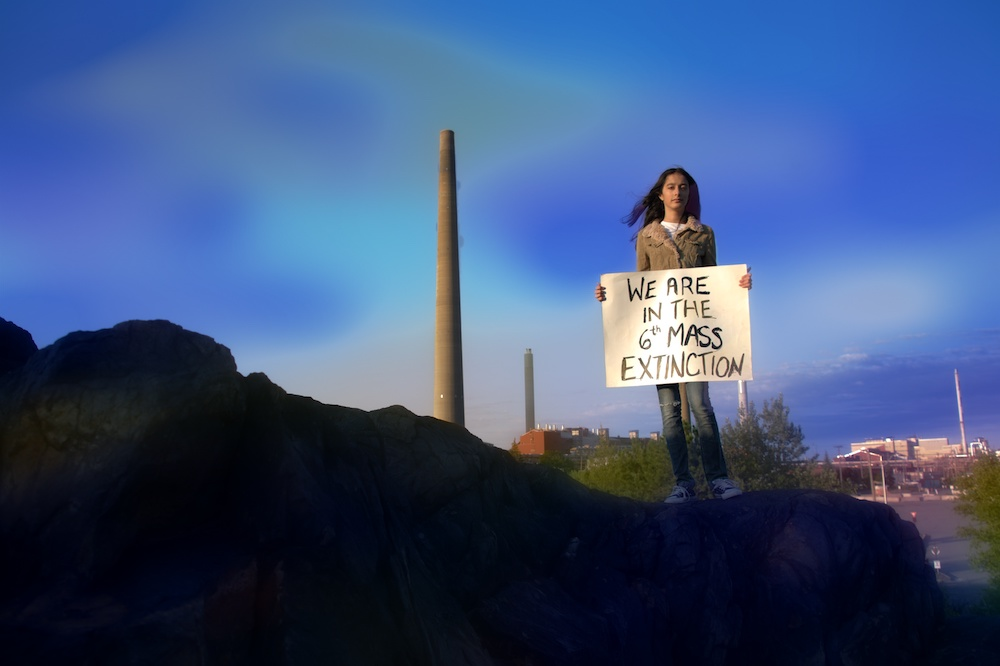"""girls stands in front of a smokestack holding a sign reading """"we are in the 6th mass extinction"""""""