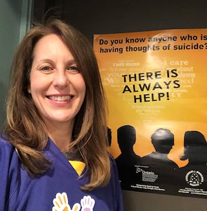 smiling woman in purple in front of a poster offering support for suicidal ideation